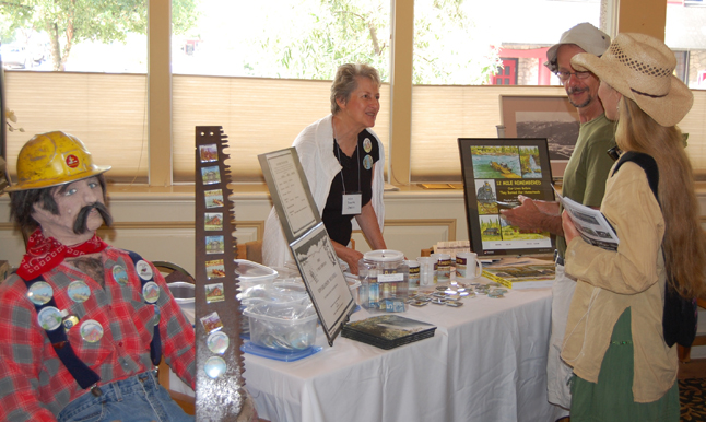 Author Ada Jarvis (left) talks with two visitors in the 2009 Homecoming registration room at the Regent Inn last Friday about her campaign to raise money to purchase a headstone for Edward Mulvehill, the first operator of the 12 Mile Ferry beginning in 1923. He died in 1938 and although Mulvehill Creek and Falls were named in his honour, he was buried without a grave marker at Mountain View Cemetery in Revelstoke David F. Rooney photo