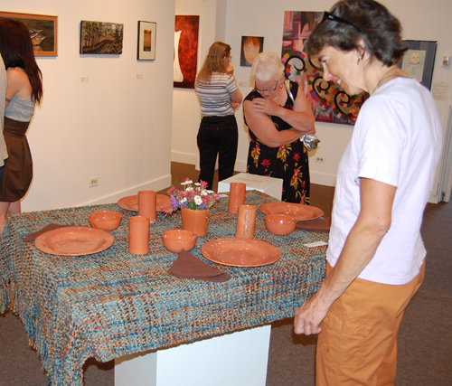 Potter Nancy Geismar examines a ceramic setting by Toni Johnston. David F. Rooney photo