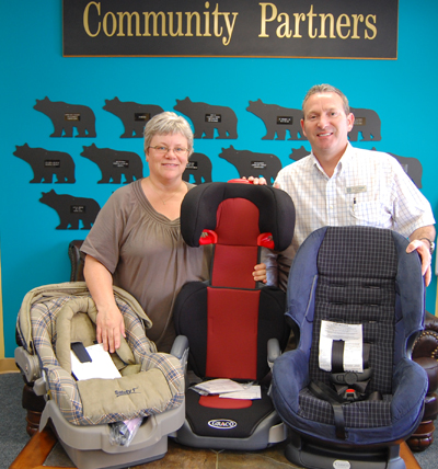 Community Connections' Patti Larson poses with Randy Driediger of Trees for Tots and some of the 16 car seats they helped purchase with a $500 donation to a BCAA Traffic Safety Foundation program that matched their donation to help needy families acquire car seats. David F. Rooney photo