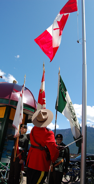 RCMP Const. Gary McLaughlin raises the flag during the Canada Day ceremony at Grizzly Plaza on Wednesday. David F. Rooney photo