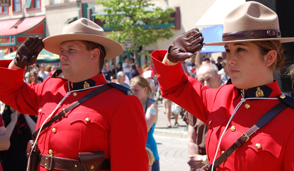 RCMP constables salute as the flag is raised during the Canada Day ceremony at Grizzly Plaza Wednesday. David F. Rooney photo