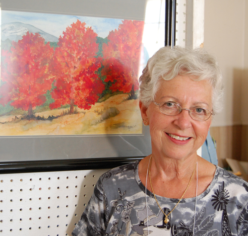 Judy Vigue poses with one of her paintings of scenes in the Arrowhead area that were on display at St. Peter's during the South Country Reunion. David F. Rooney photo
