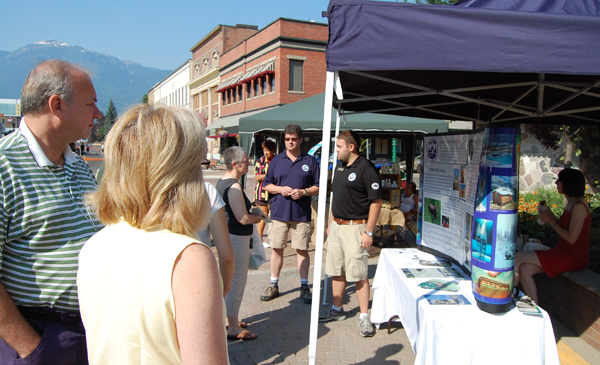 Neills Kristensen, executive director of the Friends of Mount Revelstoke and Glacier National Park, talks with curious visitors at the Farmers' Market on Saturday. Neills Kristensen