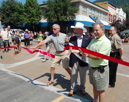 Councillor Phil Welock tries to snag the ribbon as it flies away a split second after James Baring, Lord Revelstoke snipped the ribbon to officially open the Grizzly Plaza expansion as Mayor Dave Raven looks on. David F. Rooney photo