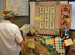 Lois Smith takes in some of the infant-sized quilts that were produced by the Quilters' Guild for the 2009 Homecoming celebration. David F. Rooney photo