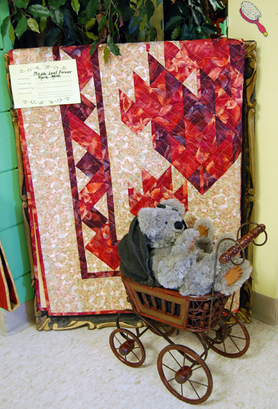 The Quilter's Guild exhibition featured all kinds of great little details such as this toy stroller with a Teddy bear, which nicely accented this piece, entitled Maple Leaf Forever, by Marie March. David F. Rooney photo