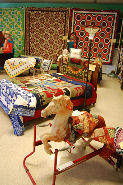 Again, the exhibitors used toys like this rocking horse to accent the work of guild members, in this case the quilts Porcelain Blue by Jill Leslie, Rise N Shine by Chris Leithwood and North of 40, Too by Irene Scarcella. David F. Rooney photo.