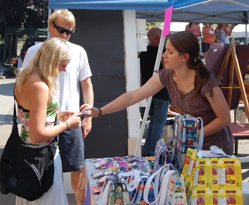 Janine Boggild talks with customers interested in her home-grown products. Janine takes discarded tetrapacks and milk or juice cartons, lines them with foil and transforms them into bags, wallets and purses. Her very distinctive products really do show the power of recycling. David F. Rooney photo