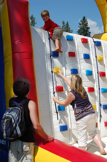 Mary Kline helps young Chaz Zaldo of Kamloops make his way down the inflatable climbing wall at the children's obstacle course set up at Queen Elizabeth Park as his father, Jose, watches. David F. Rooney photo