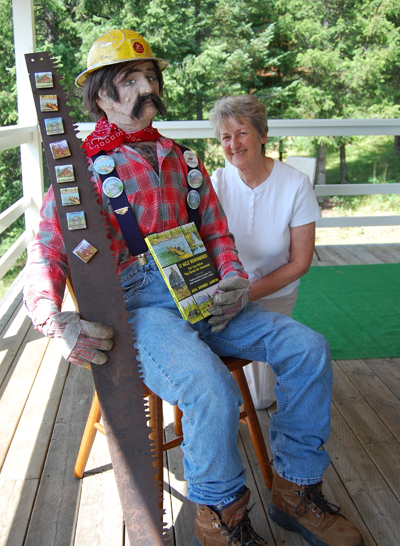 Ada Domke Jarvis, author of 12 Mile Remembered: Our Lives Before They Burned Our Homesteads, poses with the mannequin she built to help her sell special buttons and fridge magnets at Homecoming 2009. The proceeds from the sale will go towards purchasing a headstone for Edward Mulvehill, the first operator of the 12 Mile Ferry beginning in 1923. He died in 1938 and although Mulvehill Creek and Falls were named in his honour, he was buried without a grave marker at Mountain View Cemetery in Revelstoke. David F. Rooney photo