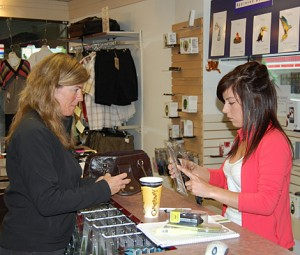 Style Trend's Lisa Hughes (right) helps a customer select the right device at the shop's Telus Mobility counter. David F. Rooney photo
