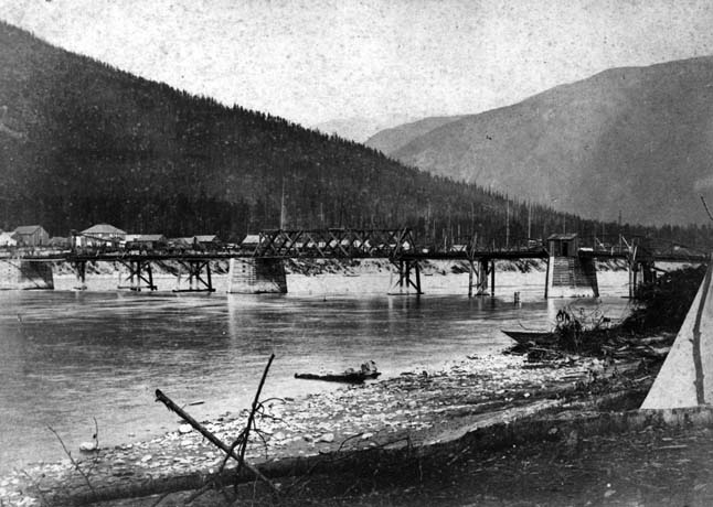 This photograph was taken in 1885, from the west bank of the Columbia River, looking toward the new settlement of Farwell, largely centered around Front Street. The bridge in the photograph was a short-lived toll bridge built by Gustavus Blin Wright. The photograph was taken by the studio of Richard and Hannah Maynard of Victoria, BC. Photo 862 courtesy of the Revelstoke Museum & Archives