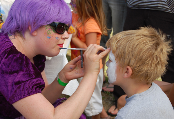 Kiki the Eco Elf paints a child's face at the Music Festival's children's area. David F. Rooney photo