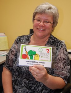 Patti Larson poses with one of the coupons being offered to eligible families in the BC Farmers' Markets' Nutrition and Coupon Project. David F. Rooney photo