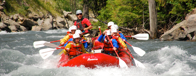 Apex Rafting Guide Dan Caldwell (wearing red in rear) shouts a command to his novice rafters as they hit white water on the Illecillewaet River. Photo courtesy of Apex Rafting