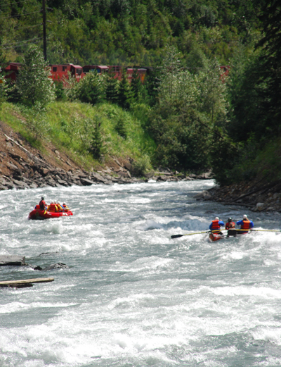 Two of Apex Rafting's craft pass a train as they make their way down the river. Photo courtesy of Apex Rafting