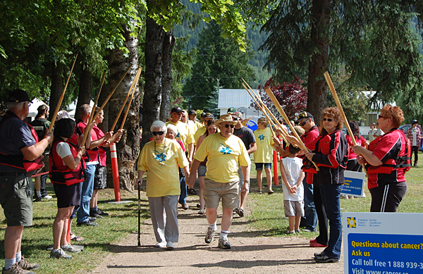 Cancer survivors march beneath the locally traditional arch of paddles hoisted by members of the Lake Revelstoke Dragon Boat Society, which counts as members many survivors of breast cancer. David F. Rooney photo