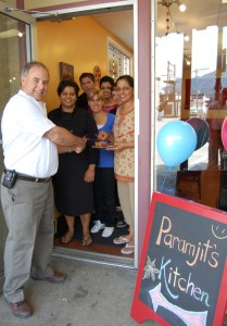 Mayor David Raven cuts the ribbon for the opening of Paramjit's Kitchen, Revelstoke's first East Indian restaurant as proprietor Goldie Sanghera (center left in black) and her mother Paramjit (center left by the door frame) and staff members looked on. David F. Rooney photo
