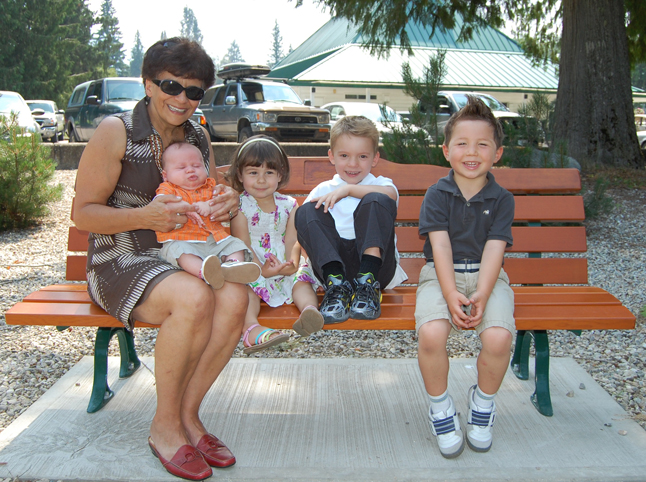 Anna Patchett sits on the bench dedicated to her late husband, Ron, with his grandchildren (from left to right) baby Alex Patterson, his big sister Mya, cousin Quintin Patchett and Ron's grand nephew Jacob Kehtler. Ron was a long-time teacher and coach at Revelstoke Secondary School whose premature death earlier this year was mourned by scores of former students.  The bench was erected near the Revelstoke Golf Course Clubhouse. David F. Rooney photo
