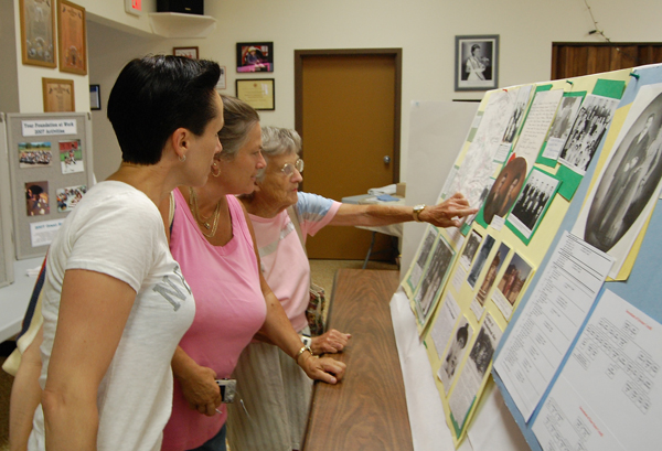 Karry Dinsdale of Cranbrook (left), her sister Barb Abel of Kelowna and their mother Ellen Fuoco of Revelstoke examne the family history on display at the Community Foundation's Family Tree display at the Fire Hall on Sunday. Hundreds of past and present residents visited the display. David F. Rooney photo