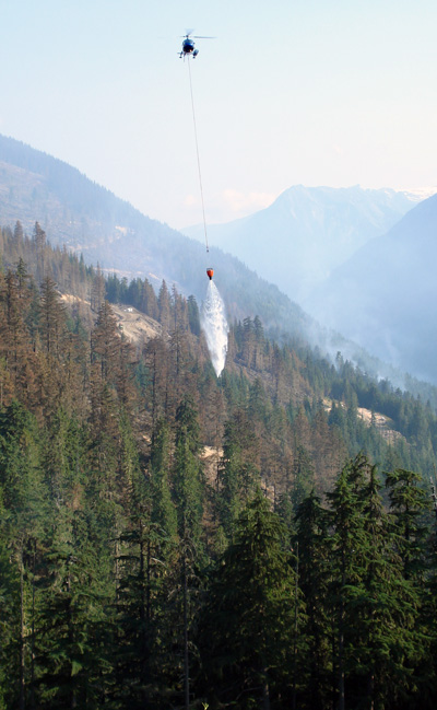 A helicopter buckets a a burning stand of trees at the Perry River Fire. Photo courtesy of Ben Parsons
