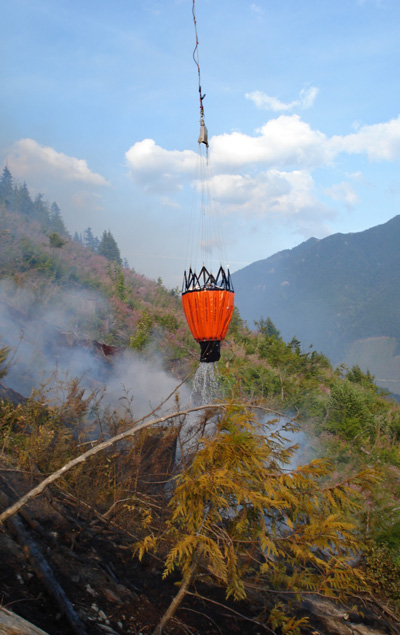 Here's something civilians don't see every day: a bucket carrying 1,200 pounds of water (that's about 143 gallons) gently douses flames at the French Creek Fire. Photo courtesy of Ben Parsons