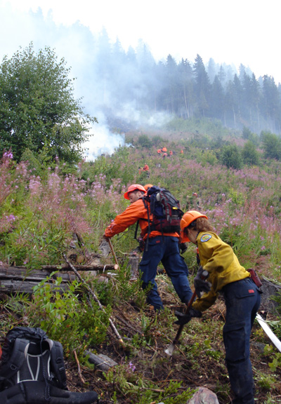 Firefighter Chris Speagle (in orange) makes his way past another firefighter to yet another part of the French Creek Fire. Photo courtesy of Ben Parsons