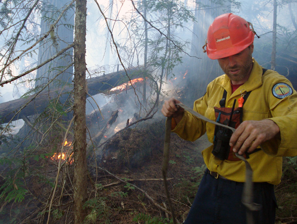 Firefighter Chris Speagle unravels a hose at the Perry River Fire. Photo courtesy of Ben Parsons
