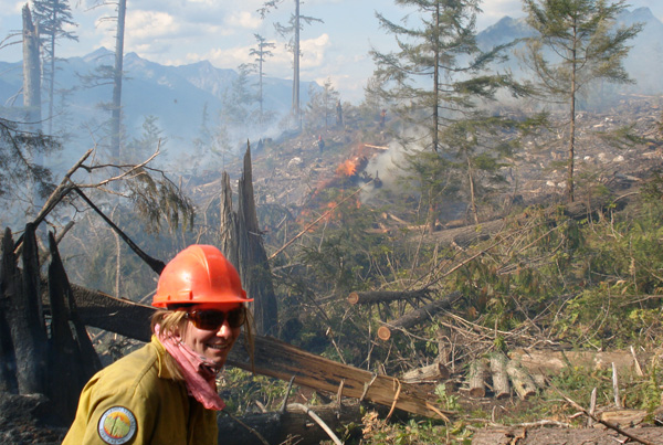 Ben Parsons' camera caught Nakimu firefighter Connie Meyer as she passes by a pile of burning slash at the Perry River Fire. Photo courtesy of Ben Parsons