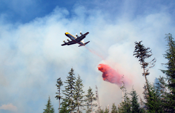 After flying back around, the tanker drops its load of fire retardant on the front line of the Perry River Fire. Photo courtesy of Ben Parsons