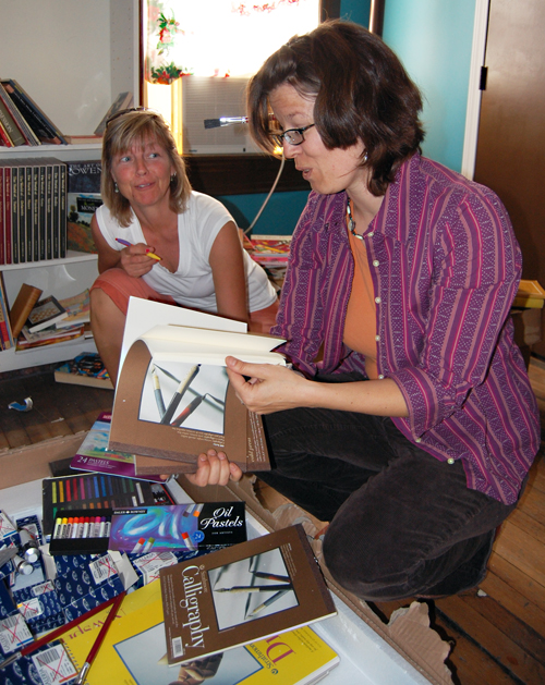 Gwen Lips (right), owner of Castle Joe Books (the new name for what was Secret Garden Books) oohs and ahs over the professional grade art supplies she is now stocking in her shop at 103 Second Street West as friend and fellow artist Tina Lindegaard looks on. David F. Rooney photo