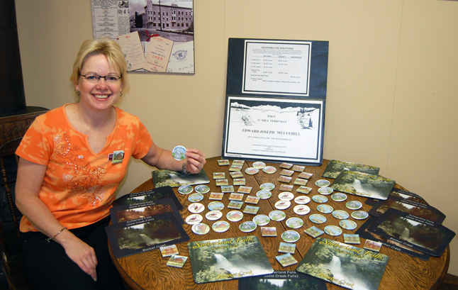 The Revelstoke Museum's Marilee Planden poses with the small display set up to raise money to purchase a headstone in the memory of 12 Mile ferryman Edward Mulvehill who was buried without a tombstone even though several local landmarks were named after him early in the last century. David F. Rooney photo