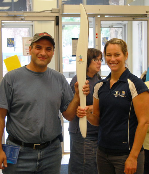 """Rob Palumbo (left) was one of the many Revelstokians who came down to the Royal Bank at Mackenzie and First Street West to meet Canadian Olympian Anne-Marie Lefrancois. The two-time Canadian alpine skiing champion and member of the team that went to the 2002 Olympics in Salt Lake City, Utah, brought the Olympic Torch to Revelstoke as part of a provincial tour. Palumbo was thrilled to meet an Olympian and even more excited to hold the torch. """"This is really something,"""" he said. """"You don't get to do this every day."""" David F. Rooney photo"""