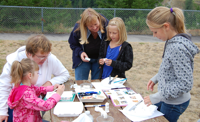 Anita May (left) watches as her granddaughter, Kassy, sketches while Sharon MacGillivray (center) looks at the carvings her nieces Sara and Katie (right) produced at the Kids' Soap Carving event at the BC Interior Forestry Museum as part of Railway Days Saturday. David F. Rooney photo
