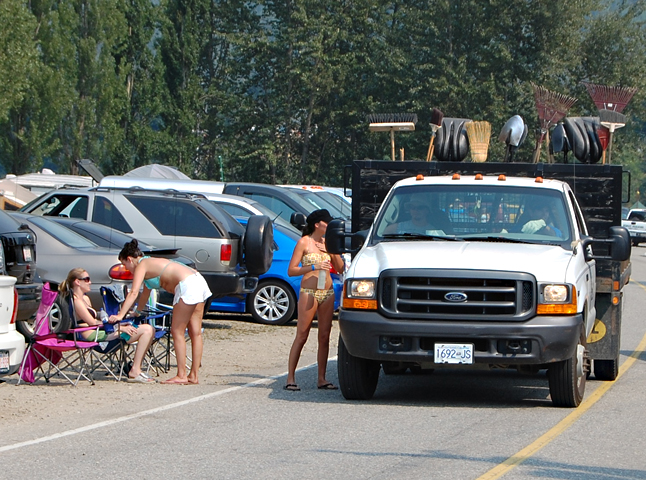 """City workers seek """"directions"""" from a young bikini-clad woman at Centennial Park on Saturday. David F. Rooney photo"""