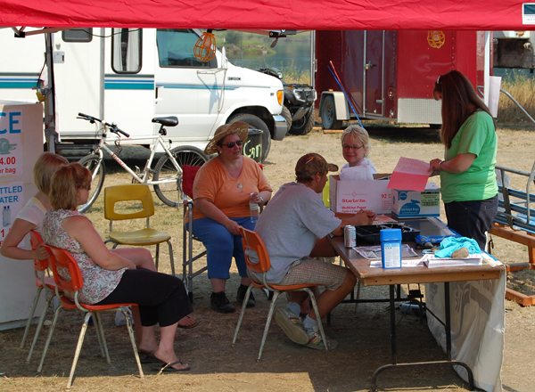 Staff at the Alcan Nancy Green tent discuss their next course of action for the grads servicing the campgrounds at centennial park. . David F. Rooney photo