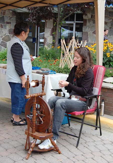 """Melody MacMillan, owner of Chiengora Fibers spins angora wool on her spinning wheel at the Farmer's Market as a potential customer examines some of the cool hats, scarves and other items she makes from angora wool and, of all things, dog hair. MacMillan said she learned the art of spinning yarn from dog hair while she was in the Yukon. """"People have been doing it for hundreds of years,"""" she said, adding that anyone who has a decent amount of hair from their pet dog is welcome to give it to her. A portion of the proceeds from the sale of items made from dog hair is donated to the Revelstoke & District Humane Society, she said. Her spinning attracted a lot of attention at the market which was particularly busy today, probably due to the number of visitors in town for Railway Days. David F. Rooney photo"""