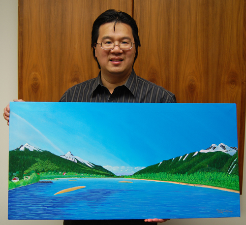 Revelstoke Community Foundation Chairman Steven Hui holds the painting that was won by a Red Deer woman. David F. Rooney photo
