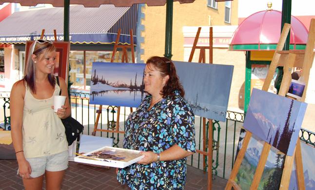 Painter Sue Davies (right) talks with Sarah Walker about her work, which she had on display in the gazebo at Grizzly Plaza during the Farmer's Market on Saturday. David F. Rooney photo