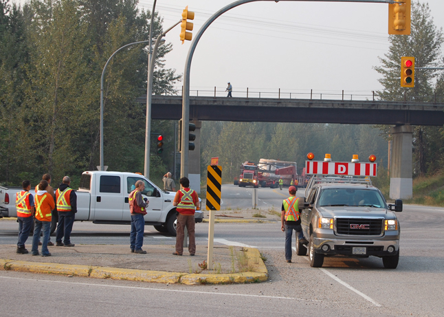 BC Hydro workers and curious onlookers stare at — and photograph — the massive transporter unit carrying the 188-tonne Unit 5 turbine as it approaches the Highway 23S intersection with the Trans-Canada Highway today (Sunday, Aug. 30). The turbine was originally scheduled to arrive some time between 1 a.m. and 3 a.m. It didn't rumble through the intersection until about 8:45 a.m. David F. Rooney photo