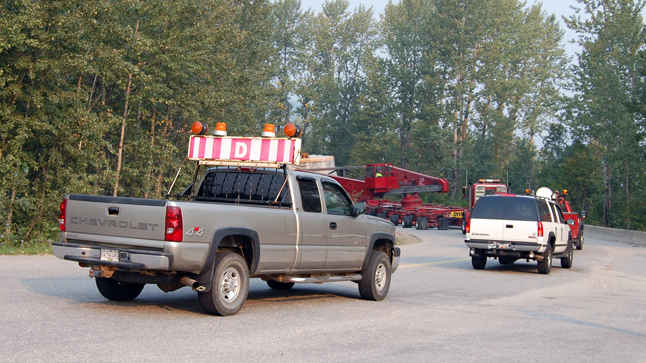 The tail end of the procession of pilot cars, trucks and the transporter itself finally slid around the first corner of Westside Road and out of view of the roughly 25 people who turned out to see the turbine. David F. Rooney photo