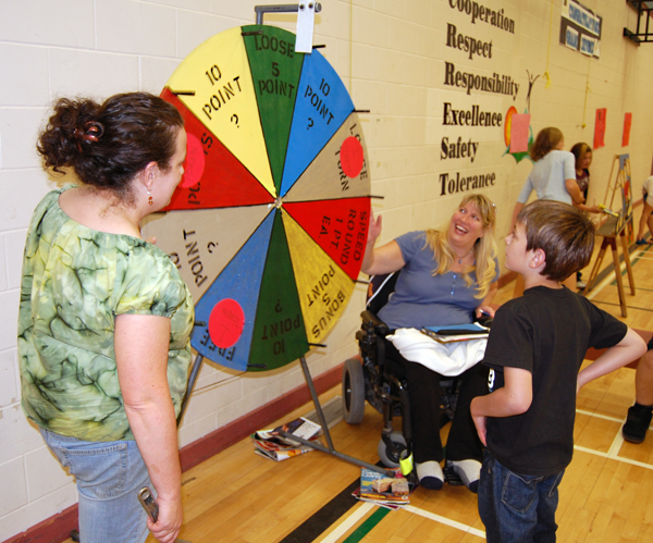 Lisa Moore (left) and Dzidra Gallicano watch as Jordan Babak tries his hand at the Wheel of Fortune at the Mount Begbie Elementary School Fall Fun Fair on Friday. David F. Rooney photo