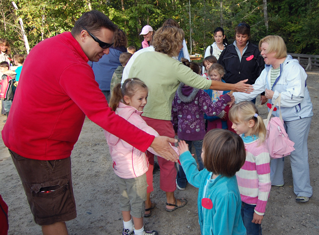 Gary McLaughlin slaps hands with a child at the start of the Kokanee Fish Festival at Bridge Creek. Slapping hands (the way fish might slap their tails) is a traditional opening to the day-long event. Organized by Mount Begbie Elementary School teacher Linda Dickson, the nine-year-old festival introduces local school children to red fish and the environment. David F. Rooney photo