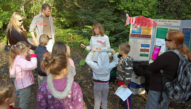 Bear Aware Coordinator Penny Page Brittin (center) talks with children at the Kokanee Fshg Festival about the relationship between bears and red fish. David F. Rooney photo