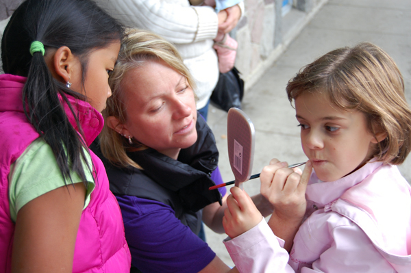 Jasmin Brackenbury paints a pretty design on Isabel Federico's cheek as her friend Abigail Brackenbury watches at the Children;s Area sponsored by the Christian City Church. David F. Rooney photo