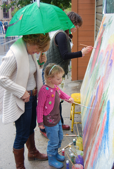 Sally Carmichael's daughter, Holly, exhibited her artistic streak by helping paint the community mural in front of Castle Joe Books. David F. Rooney photo