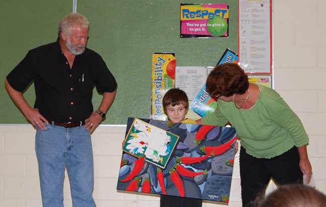Young Austin Smith holds the painting, One Fish, Two Fish, Red Fish, Blue Fish, which was presented to him by painter Davcid Rooney (left) and Revelstoke Library's Head Librarian Joan Holzer (right) at a Columbia Park Elementary School assembly today. Thomas was one of almost 300 children who entered a Summer Reading Club draw for the painting. This was the fifth year that Rooney has, in an effort to increase children's use of the library, produced a special painting for the library's SRC draws. Photo courtesy of Zone Knuff