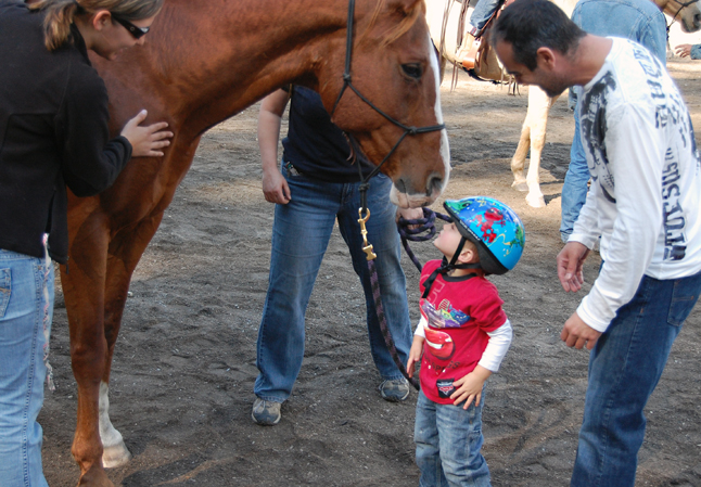 Boy meets horse as this giant equine bows down to give his diminutive rider a quick kiss. David F. Rooney photo