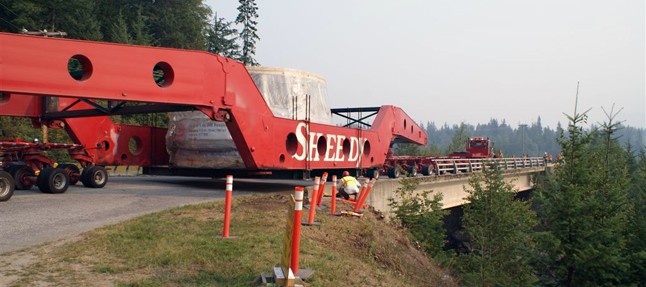 A worker peers beneath the massive transporter carrying BC Hydro's Unit 5 turbine as it negotiates the sharp curve at the head of the Westside Road bridge ovefr the Jordan River. Dusty Veideman photo courtesy of BC Hydro