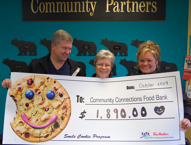 Patti Larson (center), Revelstoke's Food Bank coordinator, had a real smile on her face Tuesday when Brian and Donna Lecompte of Tim Hortons dropped by Community Connections to present her with an oversize cheque for $1,890 that was raised through the franchise's annual Smile Cookie Program. The generosity of local businesses is an important key to the continued well-being of the Food Bank. David F. Rooney photo